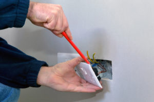 The hands of an electrician installing a power socket
